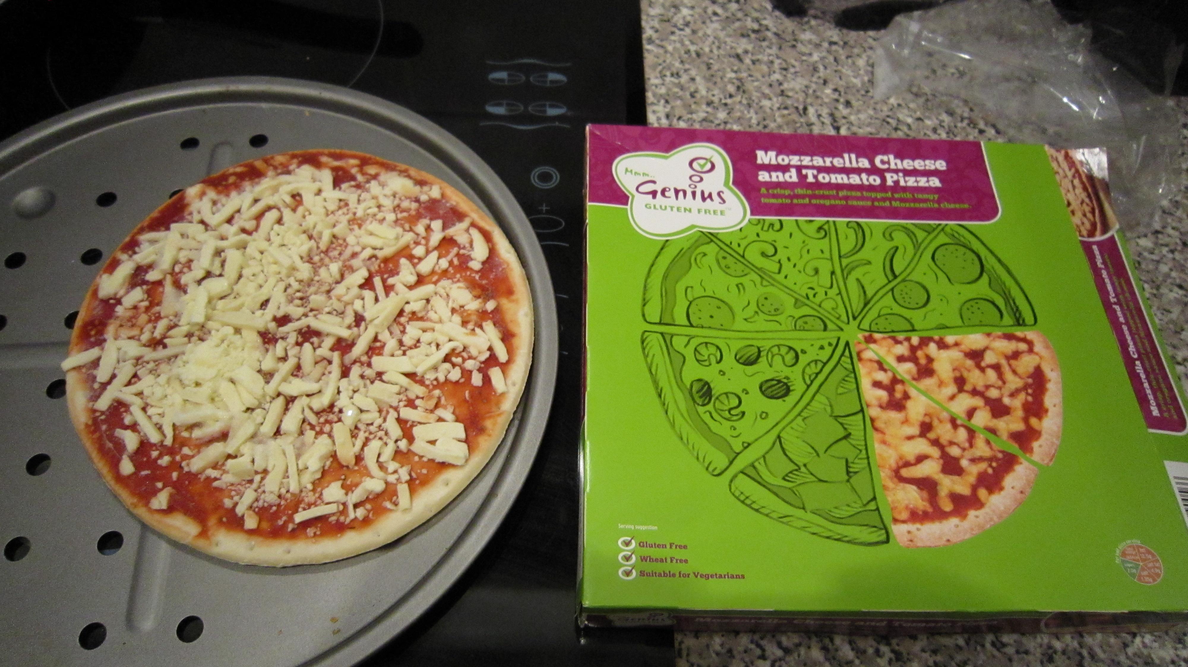 Tiny pizza sits atop a regular pizza tray